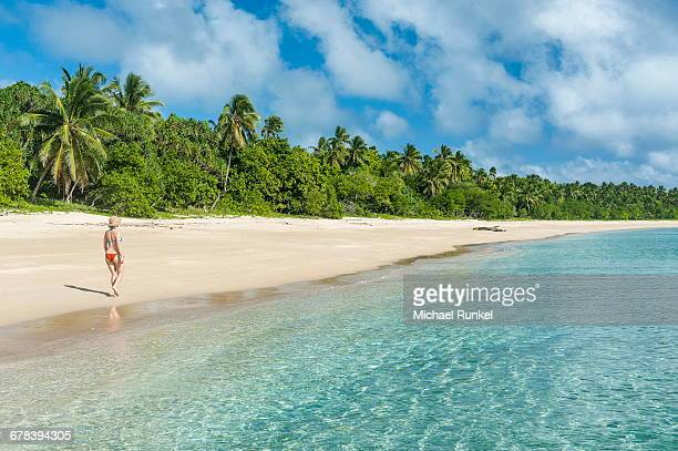 Woman walking on a palm fringed white sand beach in Haapai, Haapai Islands, Tonga, South Pacific, Pacific