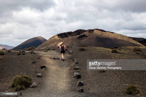 woman walking on a path near a volcano in timanfaya, lanzarote - timanfaya national park stock pictures, royalty-free photos & images