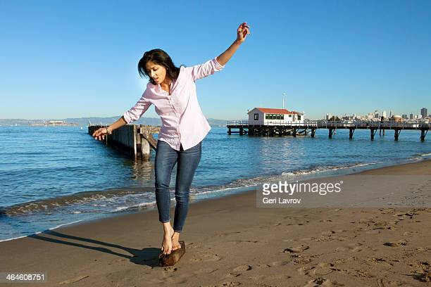Woman walking on a piece of wood at the beach