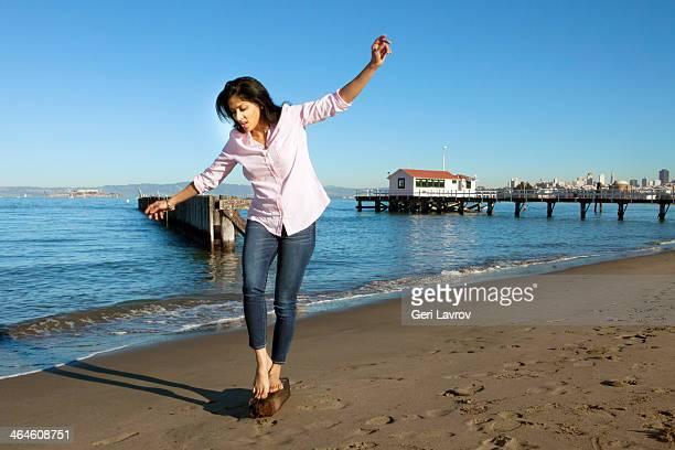woman walking on a piece of wood at the beach - calças justas - fotografias e filmes do acervo