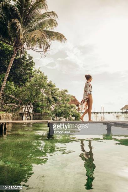 woman walking on a pier at a lagoon - idyllic stock pictures, royalty-free photos & images