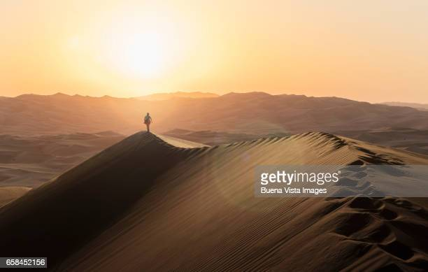 Woman walking on a sand dune at sunset