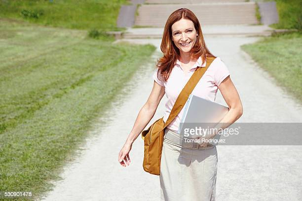 woman walking on a sidewalk - crossbody bag stock pictures, royalty-free photos & images