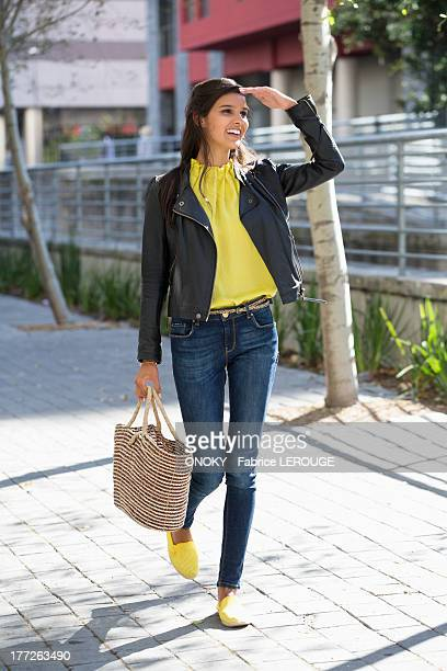 Woman walking on a street and shielding her eyes