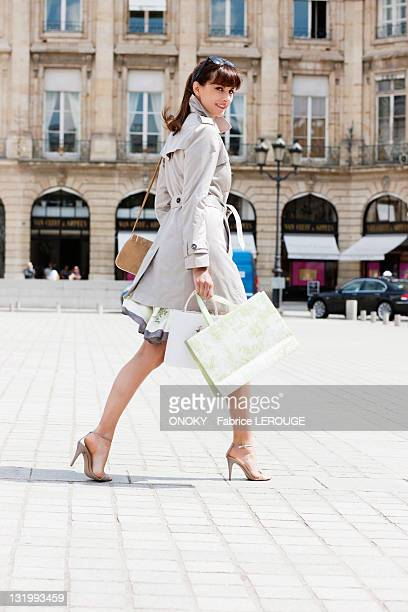 woman walking on a street, paris, ile-de-france, france - overcoat stock pictures, royalty-free photos & images