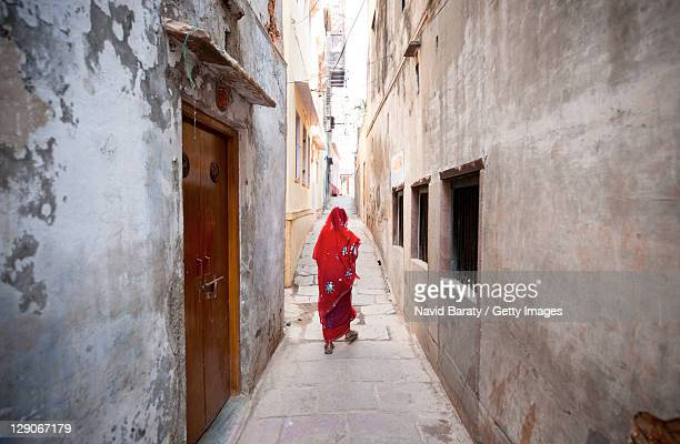 woman walking on alley - varanasi stock pictures, royalty-free photos & images