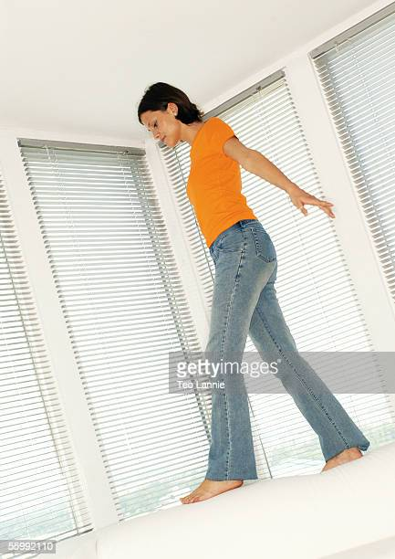 Woman walking on back of sofa, low angle view