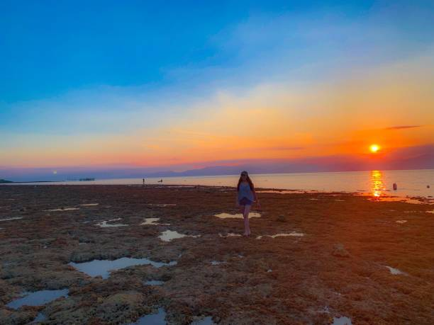 Woman Walking On Beach Against Sky During Sunset