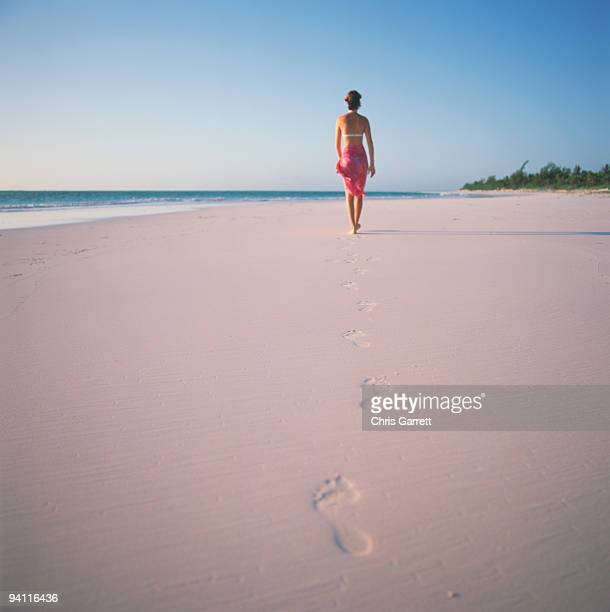 woman walking on beach at harbour island , bahamas - harbor island bahamas stock photos and pictures