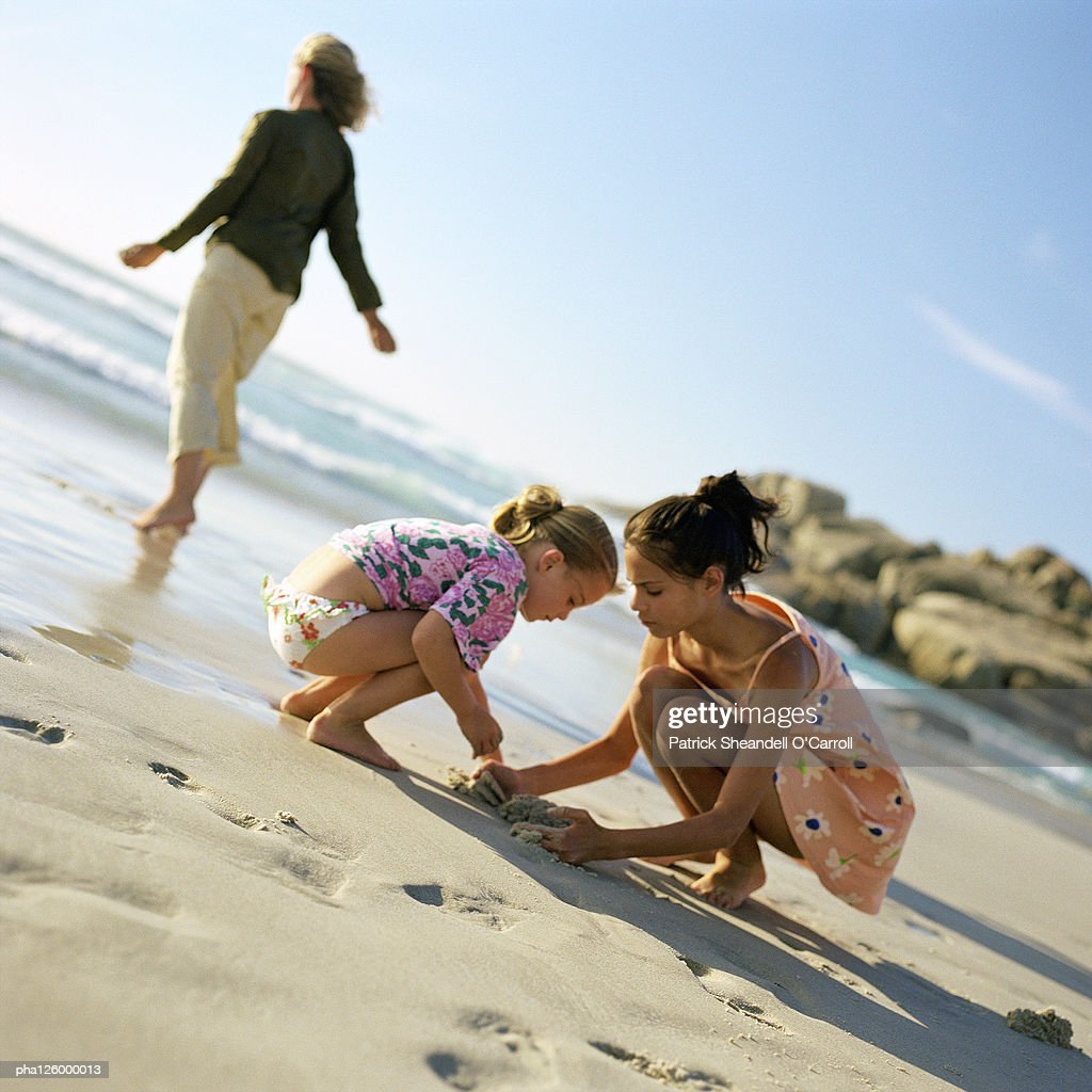 Woman walking on beach, children digging in sand : ストックフォト