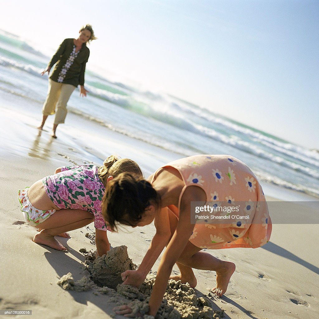 Woman walking on beach, children digging in sand : Stockfoto