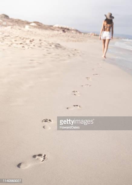 Woman walking on beach leaving footprints in sand