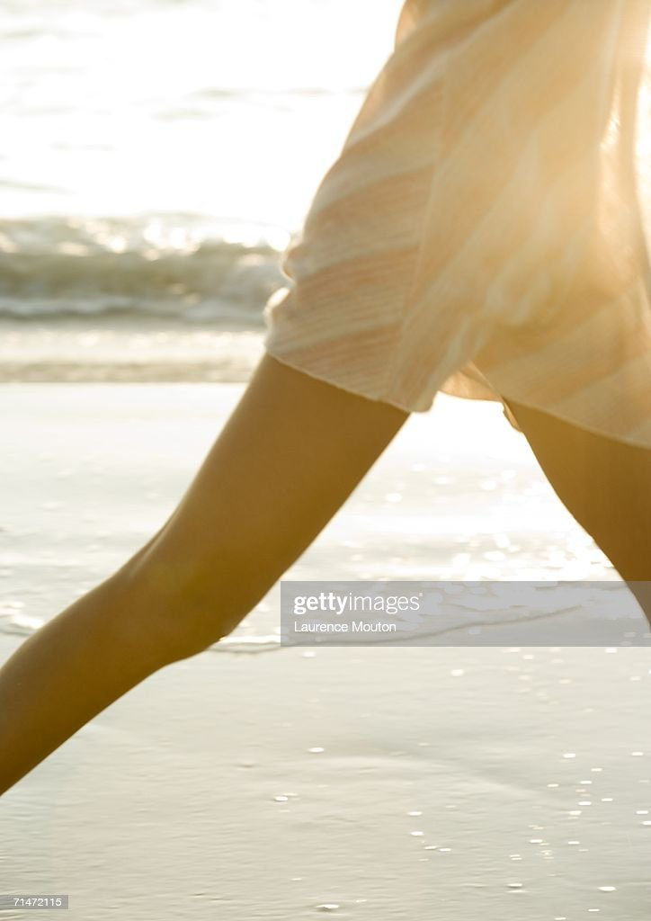 Woman walking on beach, mid section : Stock-Foto