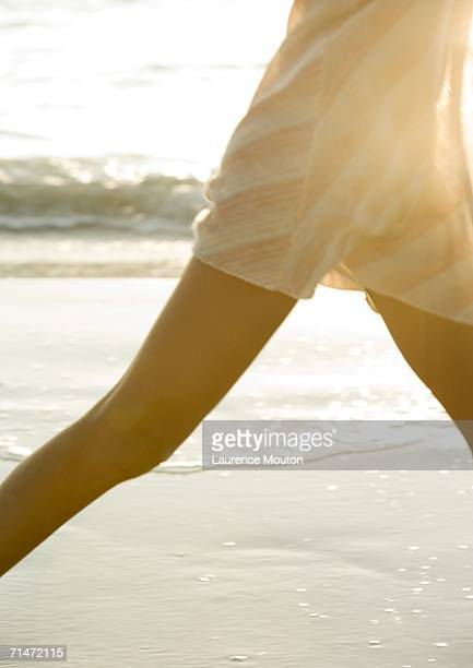 Woman walking on beach, mid section