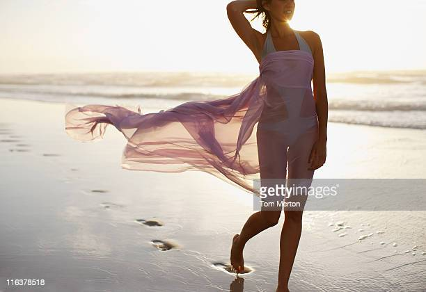 woman walking on beach - sarong stock photos and pictures