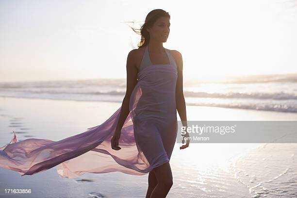 woman walking on beach - wind blowing up skirts stock photos and pictures