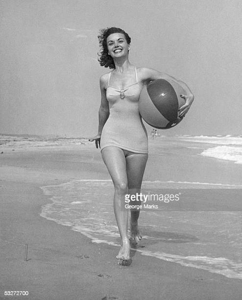 Woman walking on beach with beach ball