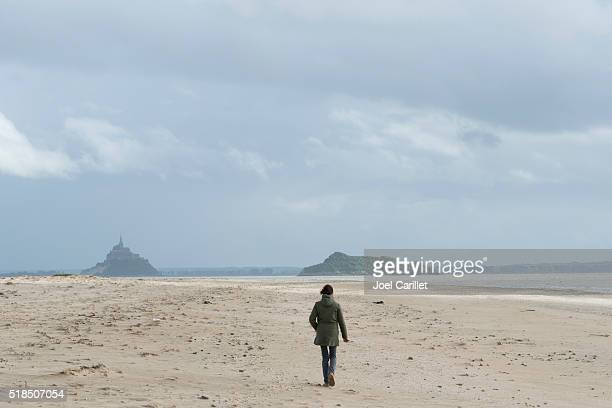 Woman walking on beach with Mont Saint-Michel in background