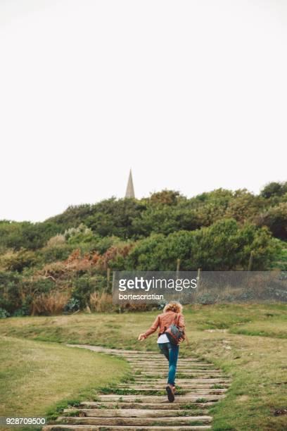 Woman Walking On Boardwalk Towards Forest Against Sky