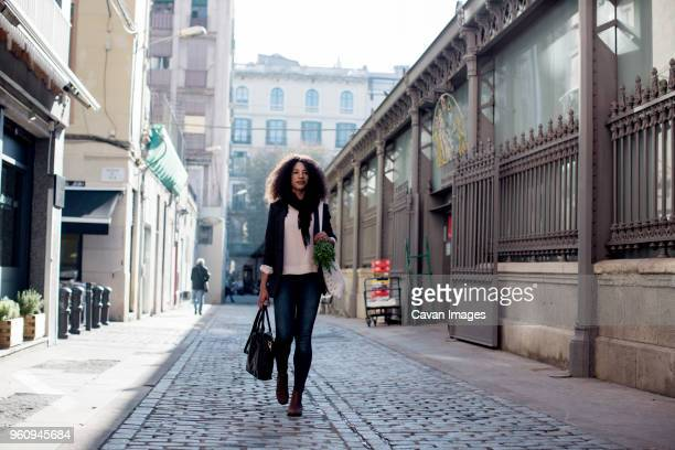 woman walking on city street amidst buildings - black purse stock pictures, royalty-free photos & images