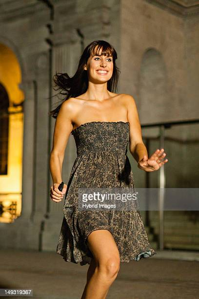 woman walking on city street at night - strapless dress stock pictures, royalty-free photos & images