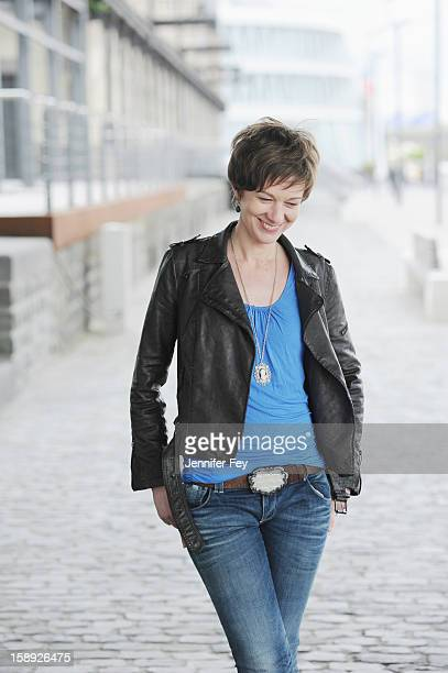 woman walking on city street - one mid adult woman only stock pictures, royalty-free photos & images