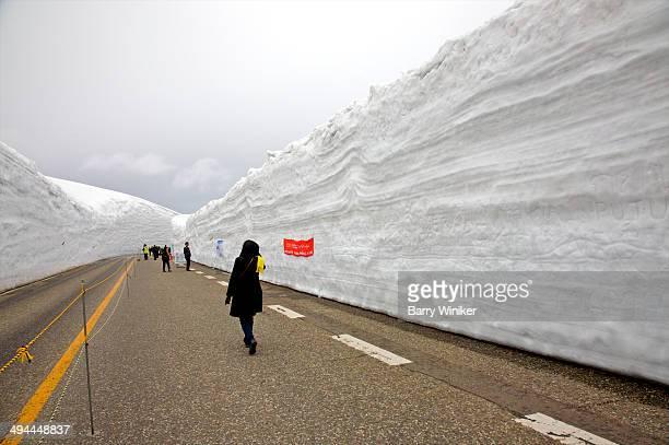Woman walking on clear road near huge snow banks