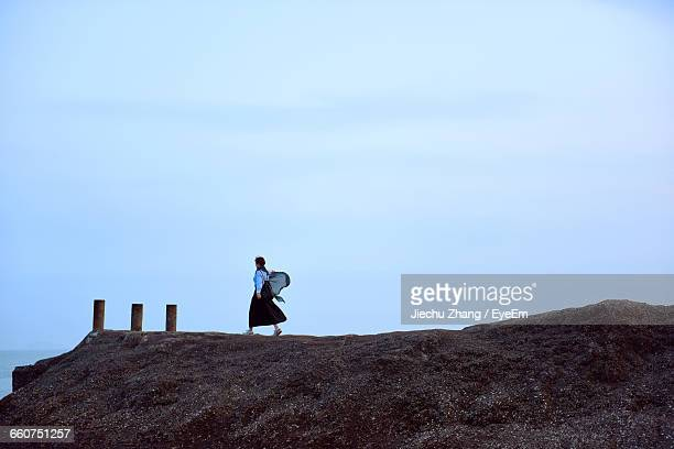 Woman Walking On Cliff Against Sky