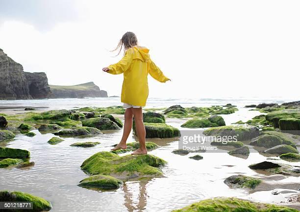 Woman walking on coastal rocks