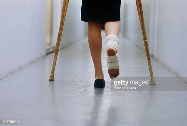 Woman Walking on Crutches in Corridor