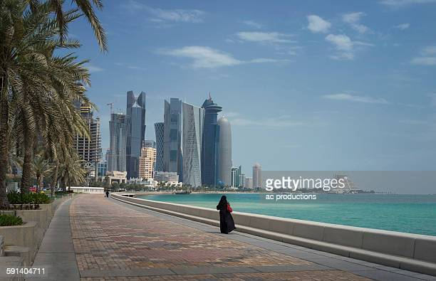 woman walking on doha waterfront, doha, qatar - doha stock photos and pictures