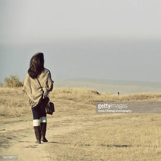 Woman walking on dry grass