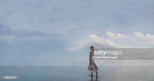 woman walking on edge of infinity pool - 白のドレス ストックフォトと画像