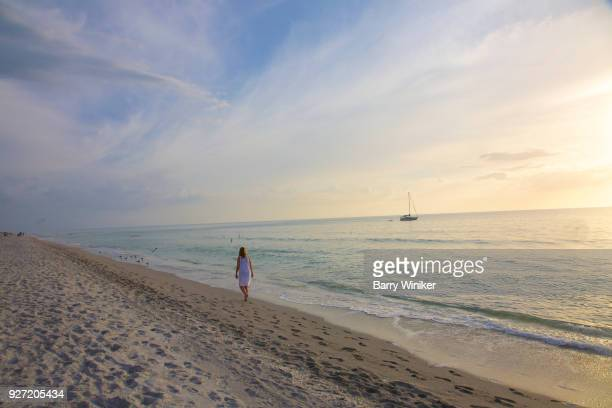 woman walking on empty beach near sunset, captiva - captiva island stock photos and pictures