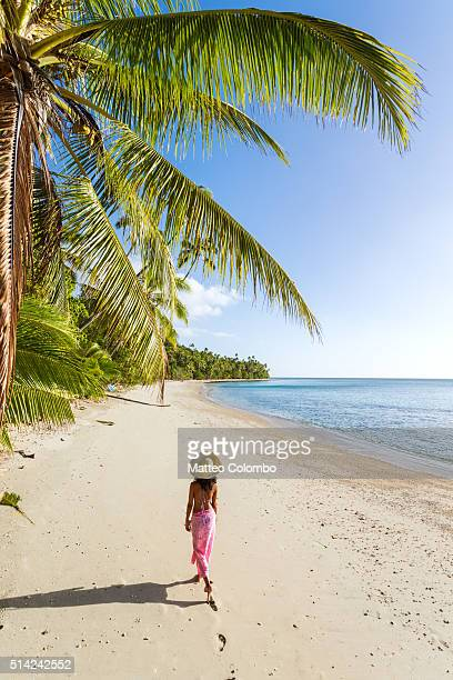 Woman walking on exotic beach on a island in Fiji