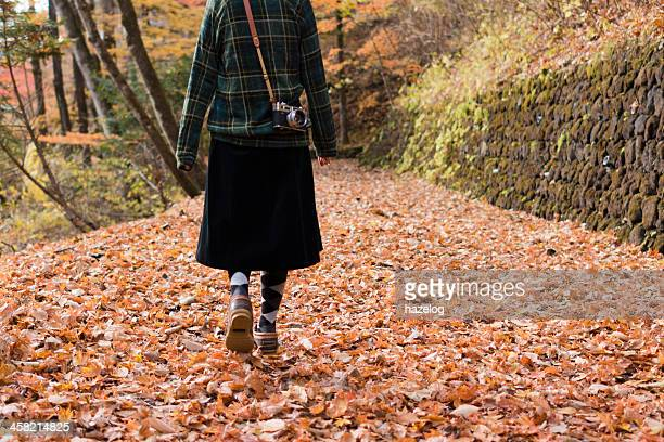 Woman walking on fallen leaves covered road