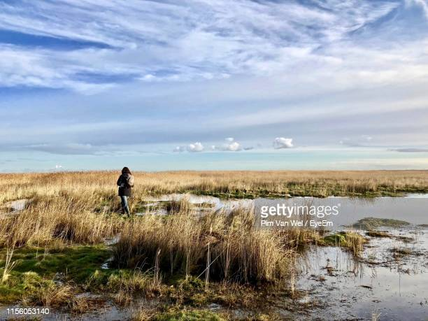 woman walking on field against sky - netherlands stock pictures, royalty-free photos & images
