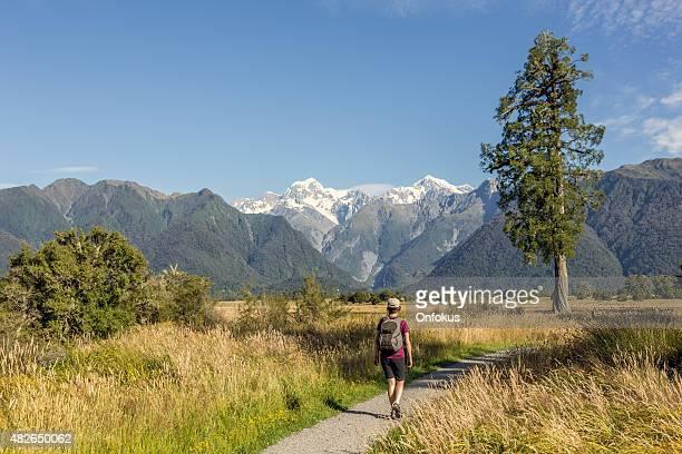 Woman walking on footpath around Lake Matheson, Westland National Park