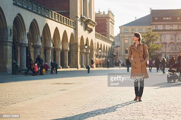 woman walking on main market square in krakow. - pedestrian zone stock pictures, royalty-free photos & images