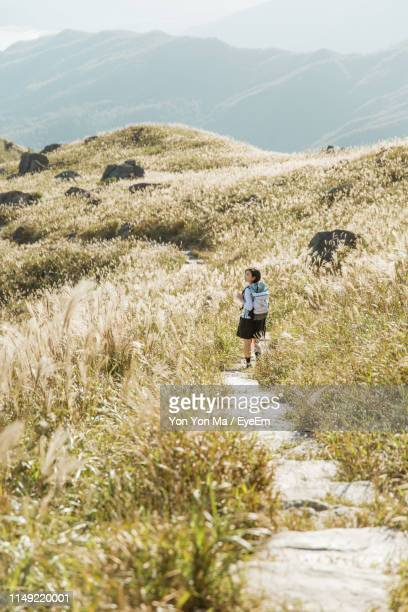 Woman Walking On Mountain Trail During Sunny Day