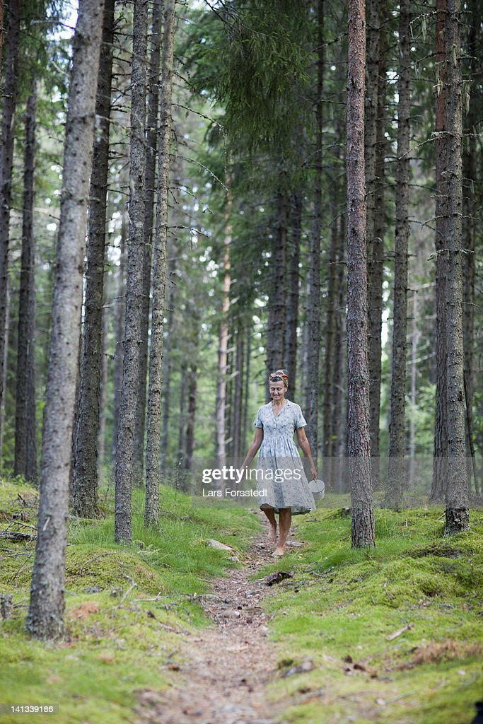 Woman walking on path in forest : Stock Photo