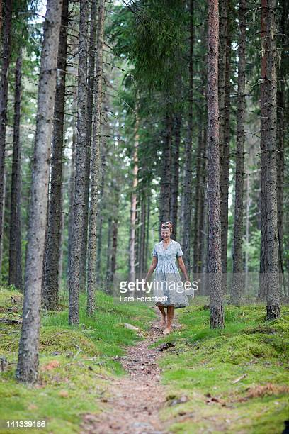 Woman walking on path in forest