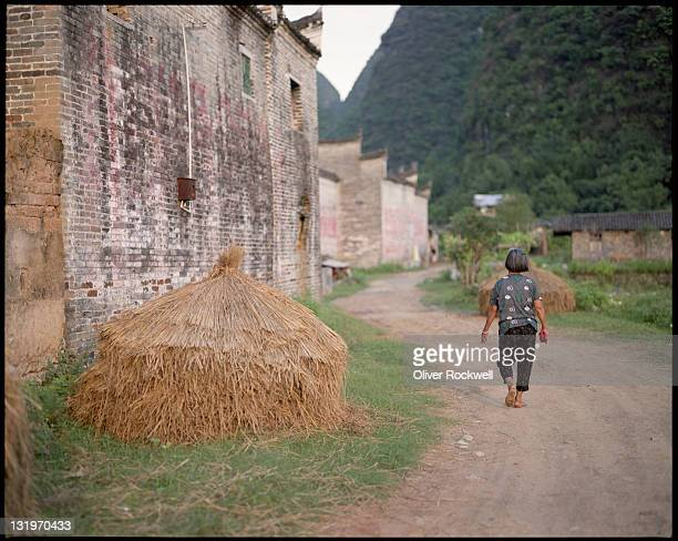 Woman walking on path with haystack
