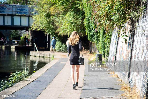 Woman Walking On Pathway Along Trees