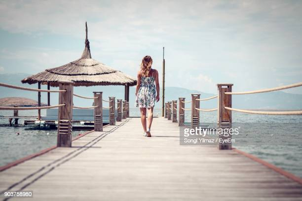 woman walking on pier by sea against sky - izmir stock pictures, royalty-free photos & images