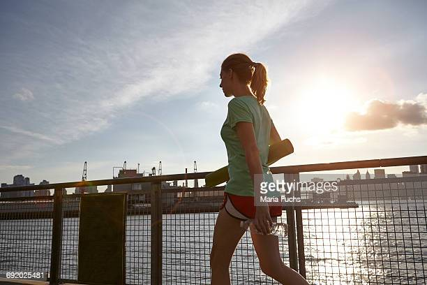 Woman walking on pier carrying yoga mat, Manhattan, New York, USA