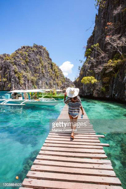 woman walking on pier, coron, palawan, philippines - standing water stock pictures, royalty-free photos & images