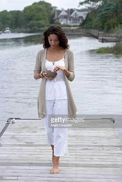 Woman walking on pier, holding bowl