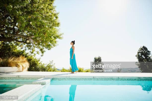 woman walking on pool deck of vacation home - long dress stock-fotos und bilder