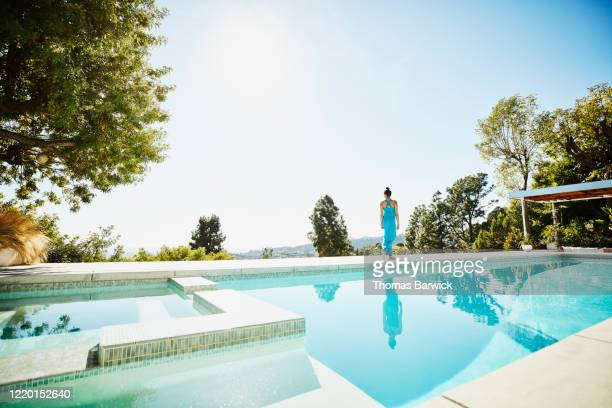 woman walking on pool deck of vacation home - holiday villa stock pictures, royalty-free photos & images